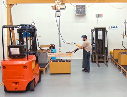 Worker charging Forklift Battery